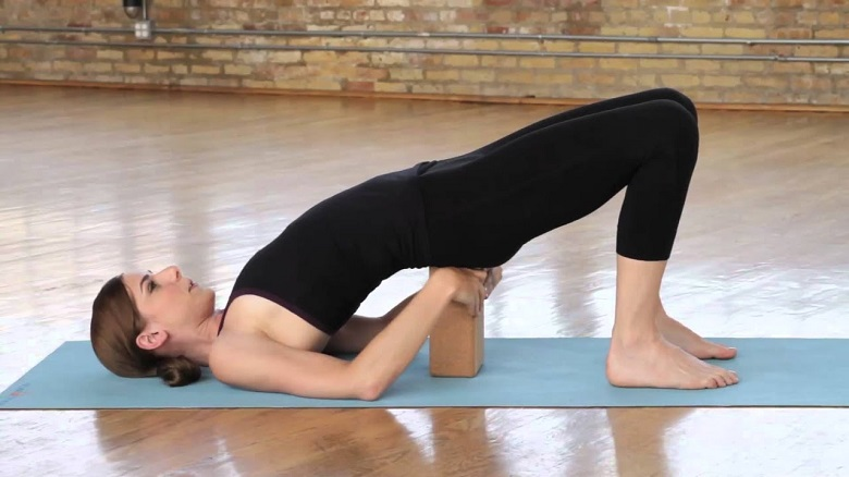 doing yoga pose with block